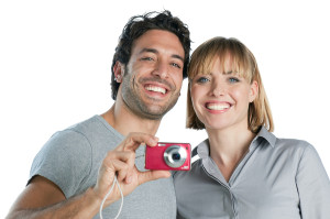 Happy joyful couple taking pictures with digital camera isolated
