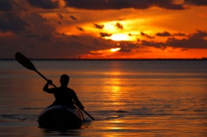 woman on kayak rowing at sunset in the ocean